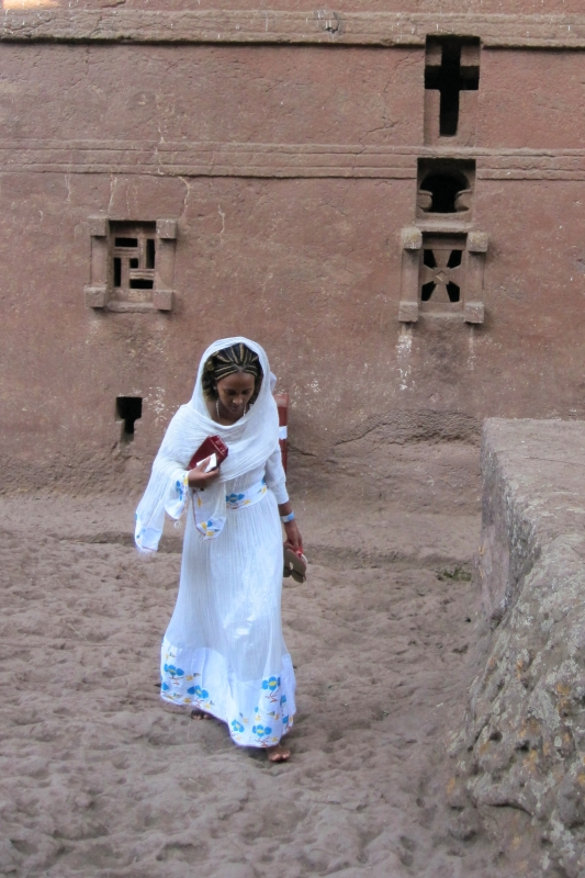 Ethiopian woman in a traditional habesha gemis dress near Bete Golghota church in Lalibela - when women go to church, they cover their hair and pull the upper ends of their shawl up their shoulders.